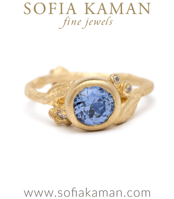Dainty, feminine, and utterly charming! Oursapphire solitaire features a 14K yellow gold twiggy textured band, diamond accented daisies and pods, and one stunning natural, No Heat blue sapphire Round Brilliant Cut center stone (0.99ct). This ring is also available in custom sizes and types of stones.Crafted by our artisan jewelers in Los Angeles. designed by Sofia Kaman handmade in Los Angeles using our SKFJ ethical jewelry process.