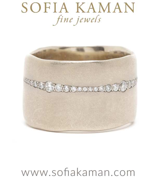 For a bolder look with a touch of glam. This 12mm ultra-wide band sheds an unexpected flash of light with a row of pavé set diamonds. This diamond line gradually tapers and widens as it wraps around the ring, mimicking the paper torn edges of the band. A truly sophisticated and artistic piece!Because of the width of this band, we recommend going up one full size in this ring.Size: 6.5 (TBD) designed by Sofia Kaman handmade in Los Angeles using our SKFJ ethical jewelry process.