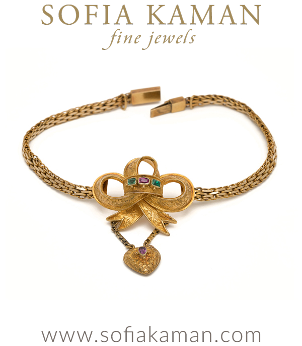 Victorian bows have got us spellbound!  This iconic 15K gold bow and drop heart bracelet charms us with its three dimensional bow, complete with ruby and emerald accents. A small compartment at the back of the heart charm is able to hold a photo of a loved one- no detail too sentimental to be spared by the Victorians, and treasured by a modern-day antiques' collector!Fitting securely on the wrist, this antique bracelet is perfect for layering and adds a well-traveled, collected look to any jewelry lover's repertoire. Original box included.   curated by Sofia Kaman