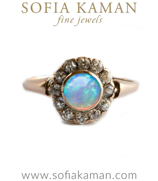 Opals have mesmerized through the ages. Many cultures have credited opal with supernatural origins and powers. Arabic legends say it falls from the heavens in flashes of lightning. The ancient Greeks believed opals gave their owners the gift of prophecy and guarded them from disease. Europeans have long considered the gem a symbol of hope, purity, and truth. The list goes on…We love opal for its romanticized history and its beauty alike! This adorable Victorian opal cluster ring (c. 1880) features one bezel set opal (approx.  0.30ct) gleaming with red, blue and green flashes, surrounded by a row of 12 Old Mine Cut diamonds (approx. 0.50 ctw, H color, VS1). Set in a 14K rosy gold, this original vintage ring makes a beautiful statement ring or unique engagement ring for an alternative bride. Please note, as opal is considered somewhat fragile for everyday use, this piece should be worn with care.Size 6 curated by Sofia Kaman